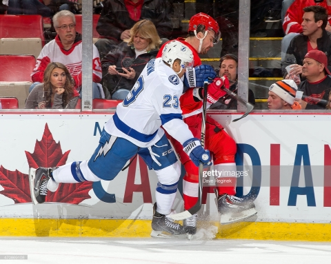 DETROIT, MI - APRIL 23: J.T. Brown #23 of the Tampa Bay Lightning rides Marek Zidlicky #28 of the Detroit Red Wings into the boards in Game Four of the Eastern Conference Quarterfinals during the 2015 NHL Stanley Cup Playoffs on April 23, 2015 at Joe Louis Arena in Detroit, Michigan. (Photo by Dave Reginek/NHLI via Getty Images)