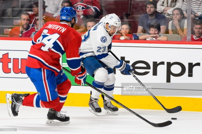MONTREAL, QC - MAY 03: J.T. Brown #23 of the Tampa Bay Lightning tries to move the puck past Greg Pateryn #64 of the Montreal Canadiens in Game Two of the Eastern Conference Semifinals during the 2015 NHL Stanley Cup Playoffs at the Bell Centre on May 3, 2015 in Montreal, Quebec, Canada. The Tampa Bay Lightning defeated the Montreal Canadiens 6-2 and take a 2-0 lead in the series. (Photo by Minas Panagiotakis/Getty Images)