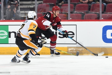 GLENDALE, AZ - JANUARY 18: Richard Panik #14 of the Arizona Coyotes plays the puck along the boards in front of Matt Cullen #7 of the Pittsburgh Penguins during the first period at Gila River Arena on January 18, 2019 in Glendale, Arizona. (Photo by Norm Hall/NHLI via Getty Images)