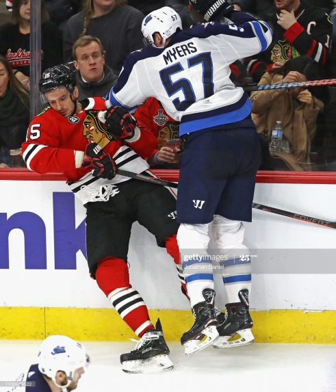 CHICAGO, ILLINOIS - APRIL 01: Tyler Myers #57 of the Winnipeg Jets checks Artem Anisimov #15 of the Chicago Blackhawks into the boards at the United Center on April 01, 2019 in Chicago, Illinois. The Jets defeated the Blackhawks 4-3 in overtime.(Photo by Jonathan Daniel/Getty Images)